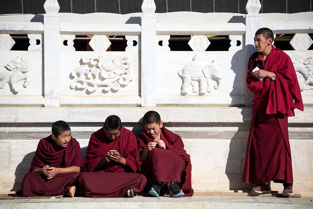 afp. hét képei - Shangri La, Kína, 2016.01.04. szerzetes játszik okostelefonon, Lamas play with their smartphones in front of the Ganden Sumtsenling Monastery in Shangri-La, Diqing Tibetan Autonomous Prefecture of southwest China's Yunnan Province on Janu