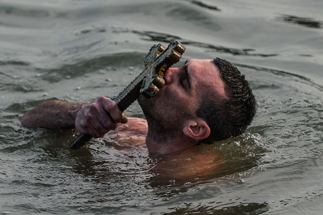afp. 2016.01.06. vízkereszt, ortodox, Isztambul, hét képei - Greek Orthodox swimmer Nicolaos Solis kisses a wooden cross retrieved from the Bosphorus river's Golden Horn, as part of celebrations of the Epiphany day at the Church of Fener Orthodox Patriarc