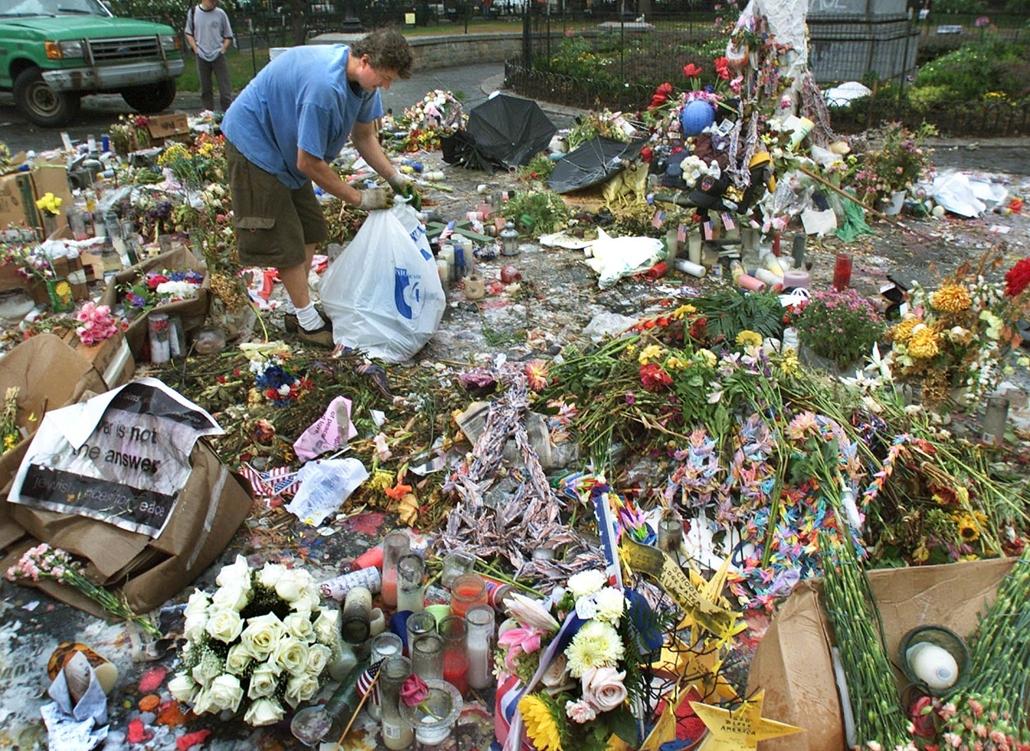 afp.01.09.11. A New York City Parkok egyik dolgozója összeszedi a virágokat egy terrortámadás áldozatai emlékére tartott megemlékezés után.