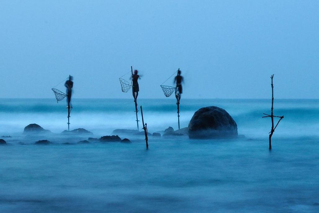 'Honorable mention', 'emberek' kategória - Sri Lanka, Midigama: hosszú expozícióval készített kép gólyaláb-halászokról, mely megmutatja, milyen stabilan állnak korallzátonyba állított rúdjaikon. - NatGeonagy