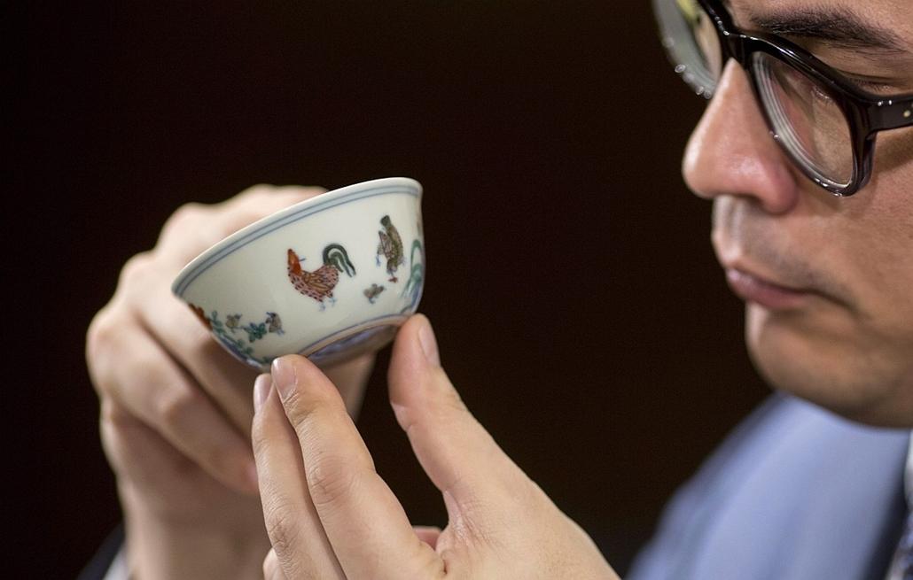 epa.14.03.12. - Hongkong, Kína: Kerámia csésze árverés - Nicolas Chow, a Sotheby's aukciósház ázsiai részlegének alelnöke és a cég kínai kerámiákban és műtárgyakban illetékes nemzetközi vezetője (k) mutat egy Csenghua-kori (1465-1487), baromfikkal és növé