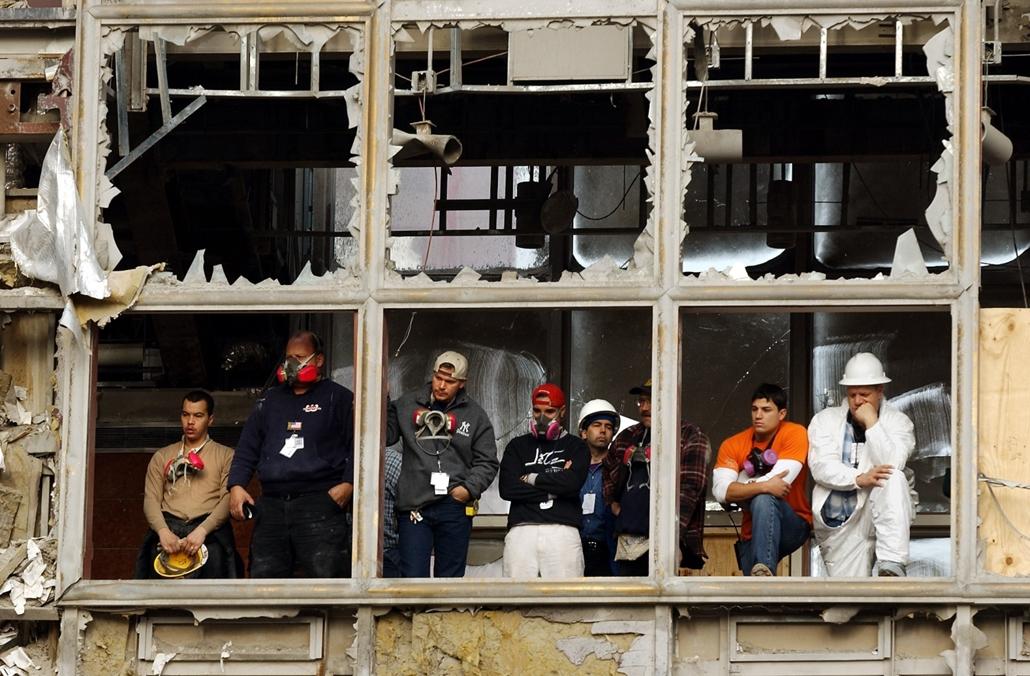 afp.01.10.11. Egy hónappal a World Trade Centert ért támadás után dolgozók néznek egy megemlékezést törött ablakokon keresztül.