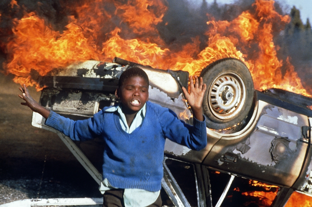 afp.85.07.10. - A South African boy dances, 10 July 1985 in Duduza township, around a car of a suspected police informer being burnt during an anti-apartheid riot, after a funeral held 10 July for four anti-apartheid activists, victims of hand-grenade bla