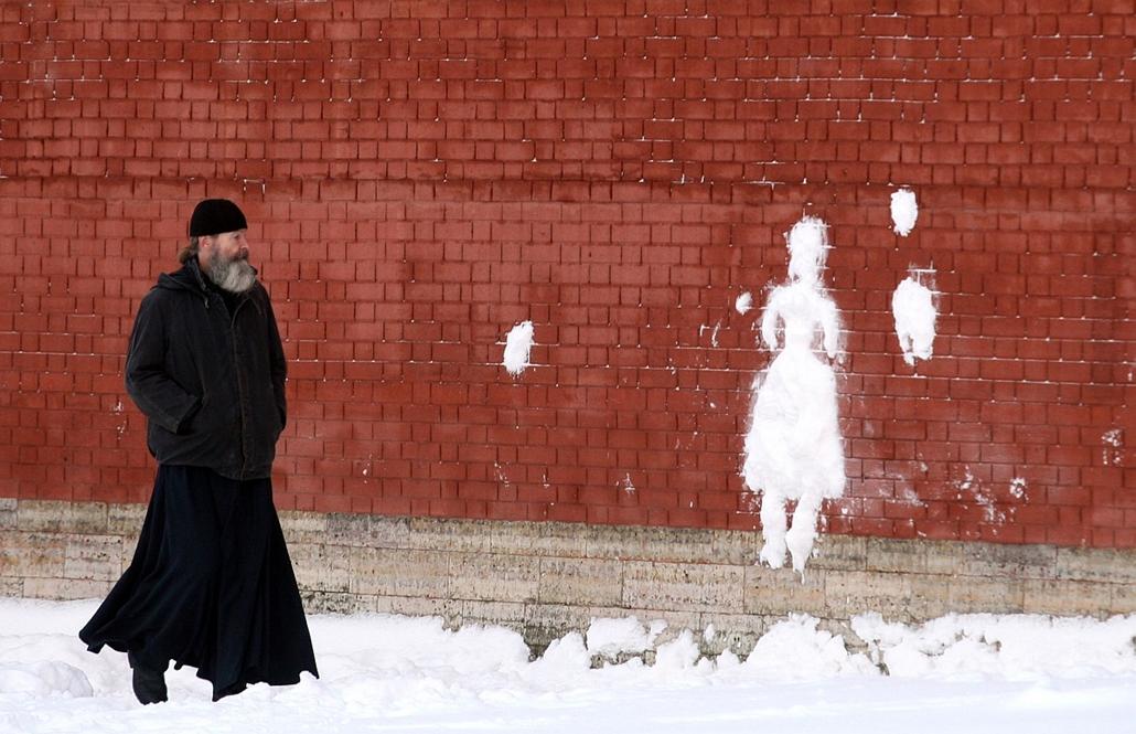 afp. hóember, 2011.01.20. Oroszország, orosz ortodox pap, hóember sziluettje, Szentpétervár, - Russian Orthodox priest looks at a silhouette made of snow on the wall of the Saint-Peter and Paul fortress in central Saint-Petersburg on January 20, 2011. Sno
