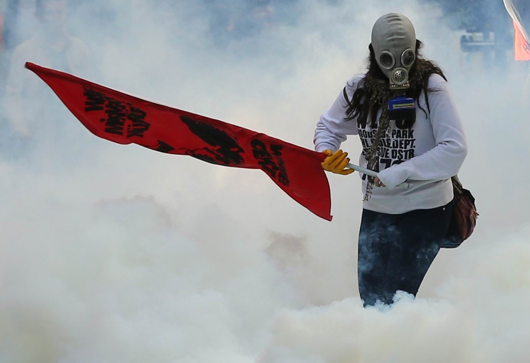 afp. hét képei - Ankara, Törökország, 2014.10.07. könnygáz, tüntetés, A person holds a flag as police uses tear gas and water cannon on October 7, 2014 in Ankara against demonstrators who protest against attacks launched by Islamic State insurgents target