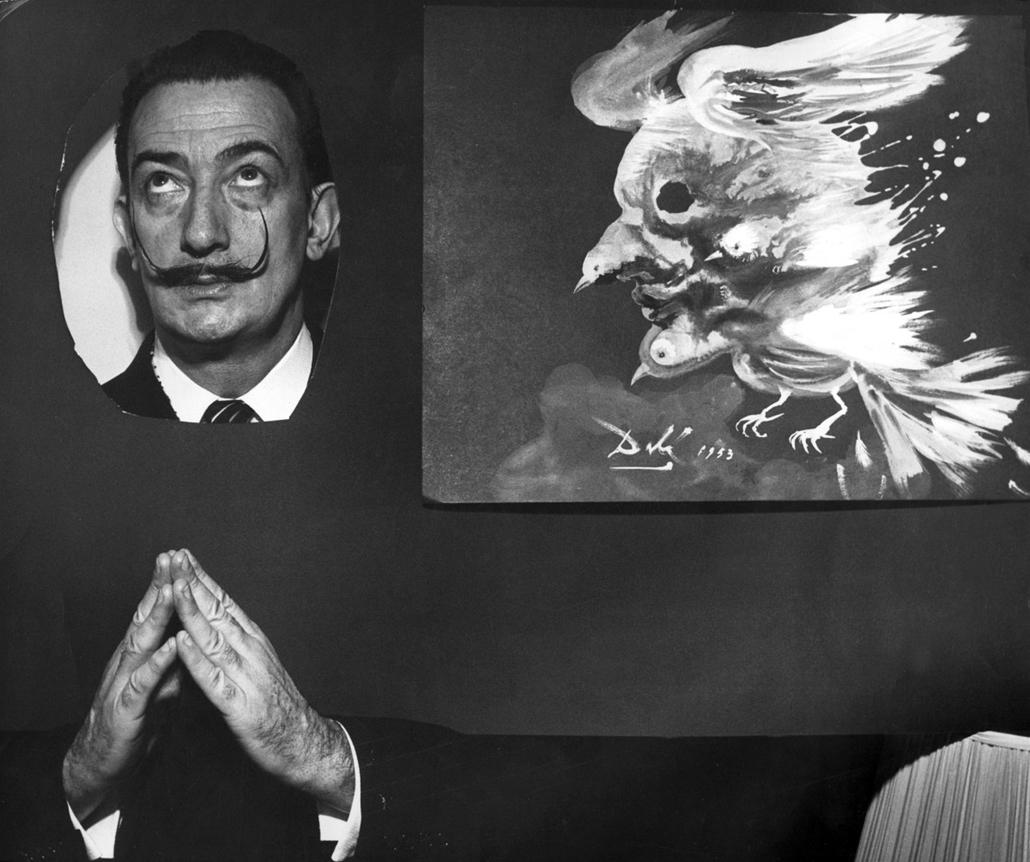 """afp. nagyítás - Salvador Dali 110 éve született - 1953.01.01. FRANCE, Paris : Photo datée de 1953 du peintre espagnol Salvador Dali, l'un des peintres les plus populaires du 20ème siècle, posant au côté de son tableau intitulé """"L'âme politique de Picasso"""""""