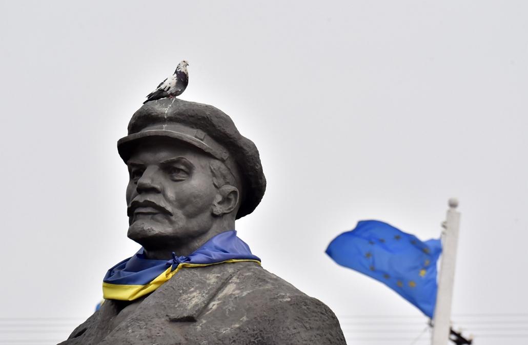 afp. hét képe - 2015.03.12. Slavyansk, Ukrajna, galamb és Lenin szobor, A pigeon sits a Soviet era statue of Lenin with a Urkainain flag wrapped around it as an EU flag flies, near the the eastern Ukrainian city of Slavyansk, Donetsk region, controlled by