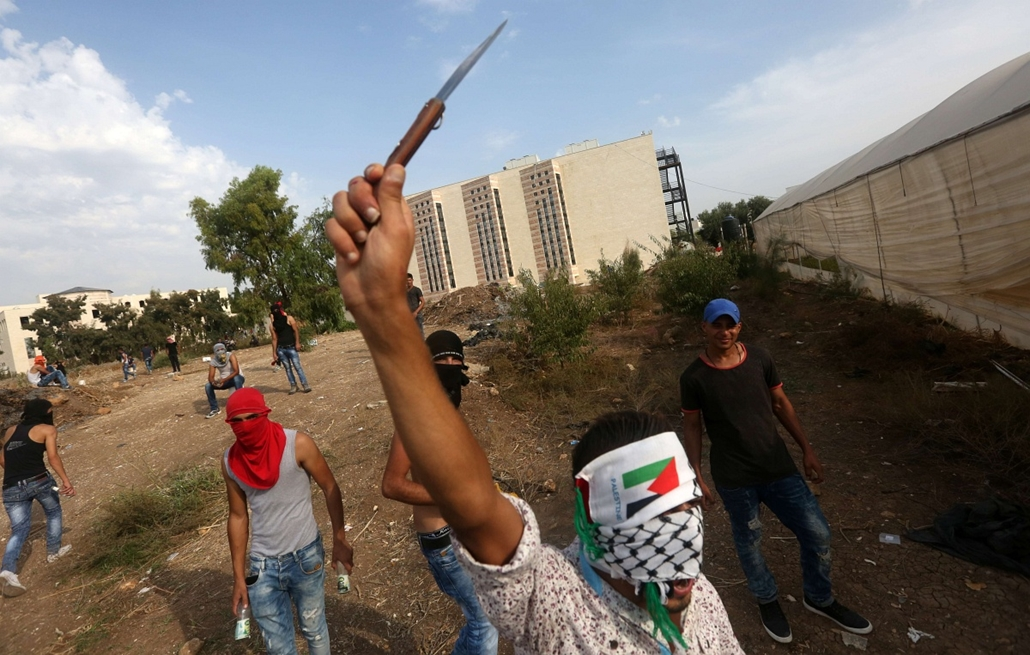 afp. izraeli-palesztin konfliktus 2015 -TULKAREM 2015.10.18. A Palestinian youth raises a knife during clashes with Israeli security forces (unseen) in the West Bank city of Tulkarem on October 18, 2015. Four Palestinians were shot dead and a fifth wounde