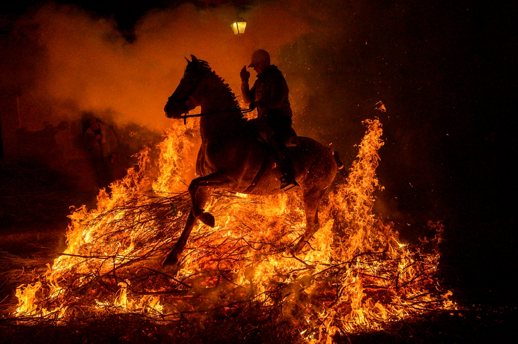 """NAGYÍTÁS ÉV KÉPEI A horseman jumps over a bonfire in the village of San Bartolome de Pinares in the province of Avila in central Spain, during the opening of the traditional religious festival """"Luminarias"""" in honour of San Antonio Abad (Saint Anthony), pa"""
