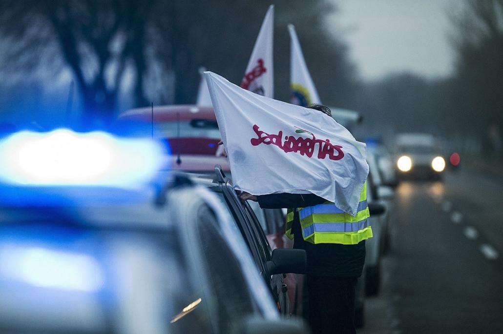 mti. Útlezárások - 2014.12.15.  Kecskemét,  A Szolidaritás zászlaját teszi ki egy férfi az autójára a LIGA Szakszervezetek forgalomlassító demonstrációján a 44-es főúton Kecskemét határában 2014. december 15-én.