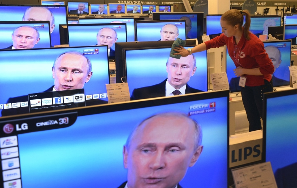 afp. Vlagyimír Putyin tv, tévében - 2014.04.17. Oroszország, Moszkva - An employee wipes a TV screen in a shop in Moscow, on April 17, 2014, during the broadcast of President Vladimir Putin's televised question and answer session with the nation. Putin ac