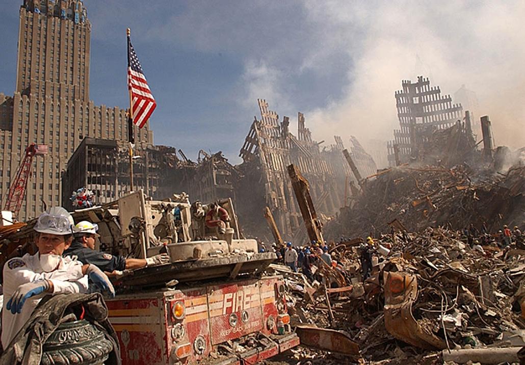 afp.01.09.18. Tűzoltók és  városi mentőalakulatok próbálják eloltani a még parázsló tüzeket hat nappal a terrortámadás után, miközben túlélők után kutatnak.