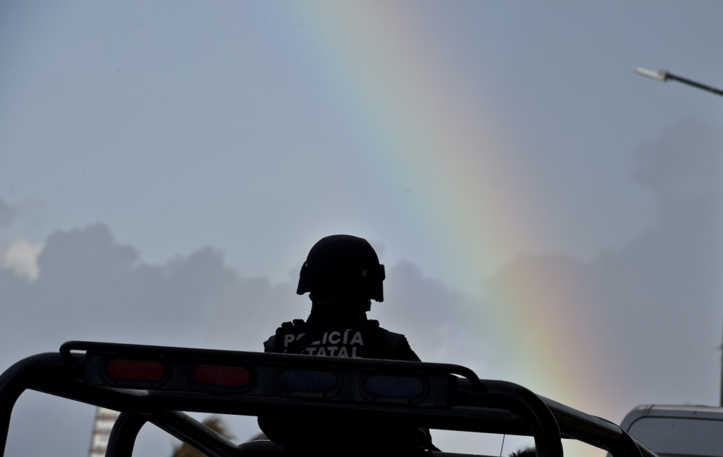 afp. hét képei - Veracruz, Mexikó, 2014.12.07. A member of the state police stands guard over a truck as a rainbow is seen along the coast in Veracruz, Mexico on December 7, 2014, one day before the start of the XXIV Ibero-American Summit.