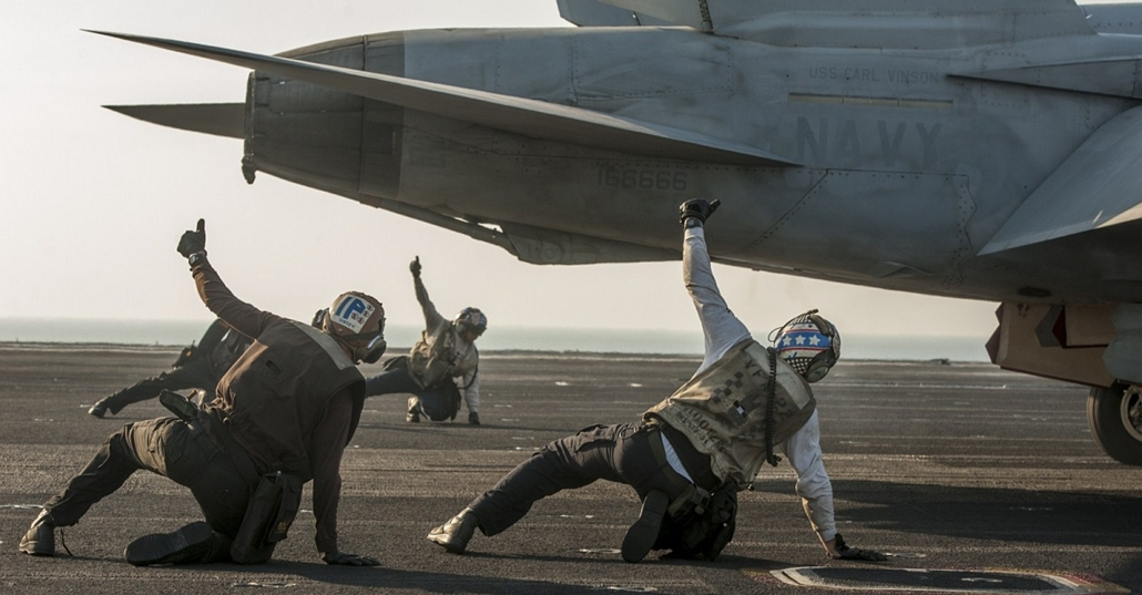 afp. hét képei - 2014.12.11. This US Navy photo obtained December 11, 2014 shows sailors assigned to the Fighting Redcocks of Strike Fighter Squadron (VFA) 22 signal that an F/A-18F Super Hornet is ready to be launched from the flight deck of the Nimitz-c