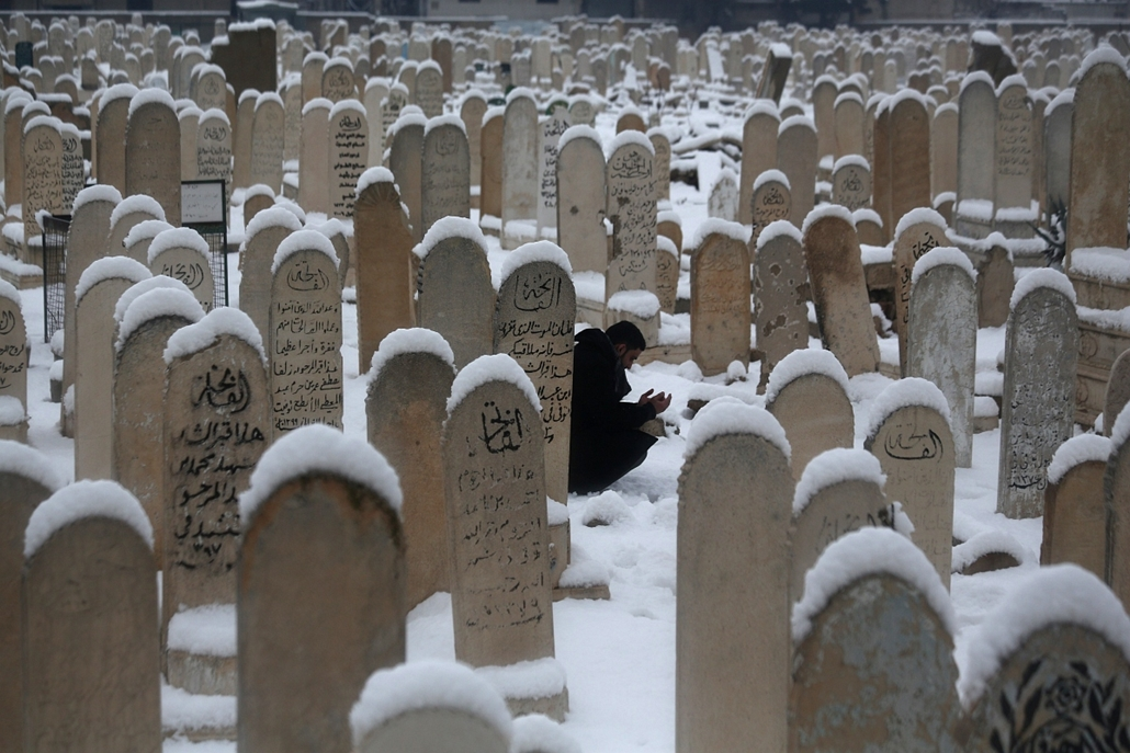 afp. Douma, Szíria 2015.01.07. megemlékezés, temető, sírkövek, A man prays by his grandfather's gave at a graveyard covered in snow in the rebel-held city of Douma, northeast of the capital Damascus, on January 7, 2015, as a major snow storm hit the Middl