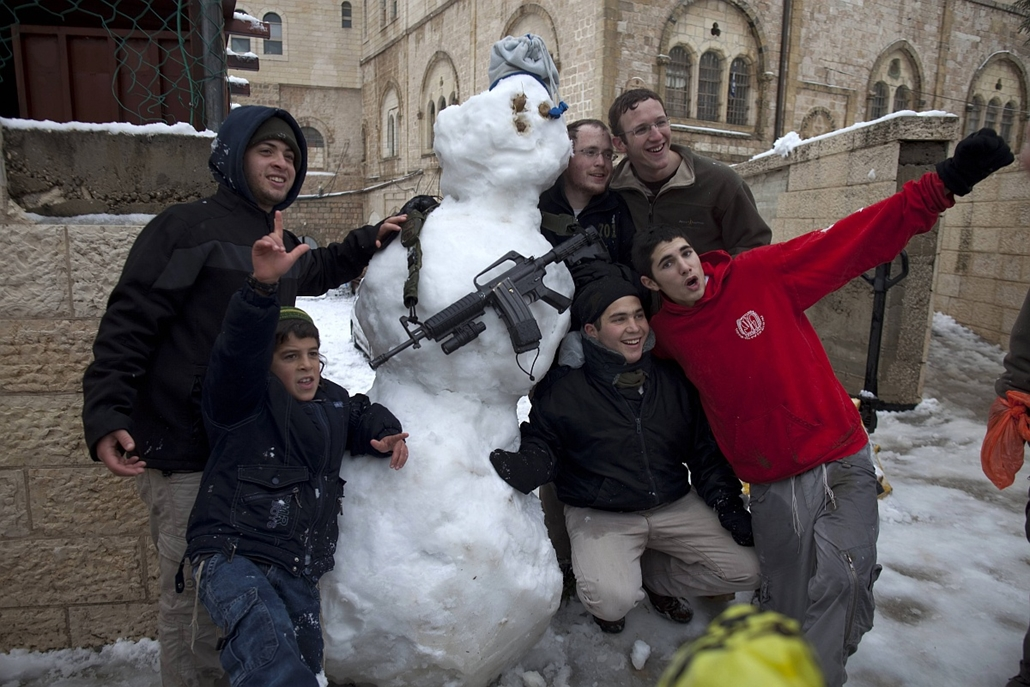 afp. hóember, 2012.03.02. ciszordánia, Hebron, puska, fegyver, zsidó telepesek, - Jewish settlers pose for a picture with a snowman armed with an M-16 rifle in the West Bank city of Hebron as wintry weather swept through the region on March 2, 2012.