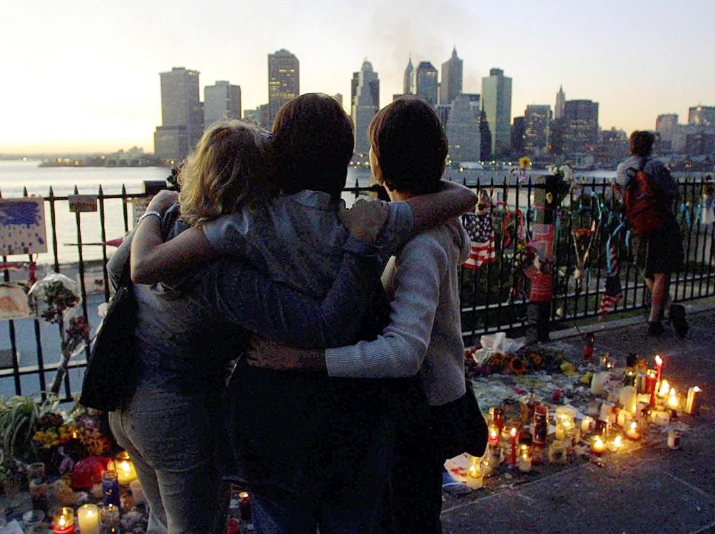 afp.01.09.16. Három nő ölelkezik a Brooklyn Sétányon szeptember 16-án. A World Trade Center tornyai közül még több nappal a terrortámadás után is füst gomolyog.