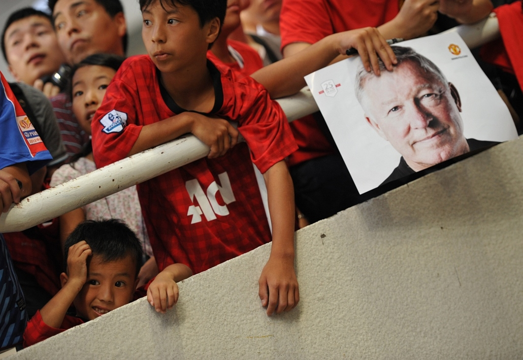 Alex Ferguson nagyításhoz - CHINA, Shanghai : A Manchester United fan holds a photo of manager Alex Ferguson (R) as they wait for the team to arrive for a team training session at Shanghai Stadium in Shanghai on July 24, 2012. United are in China as part