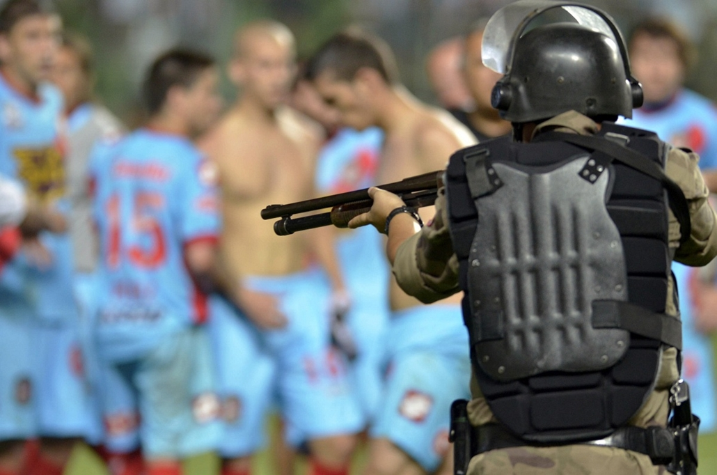 Libertadores Kupa 2013 - An armed policeman stands alert near Argentinian Arsenal players (in background) after their football match against Atletico Mineiro for the Libertadores Cup 2013 at Independencia Arena in Belo Horizonte, Minas Gerais state on Apr