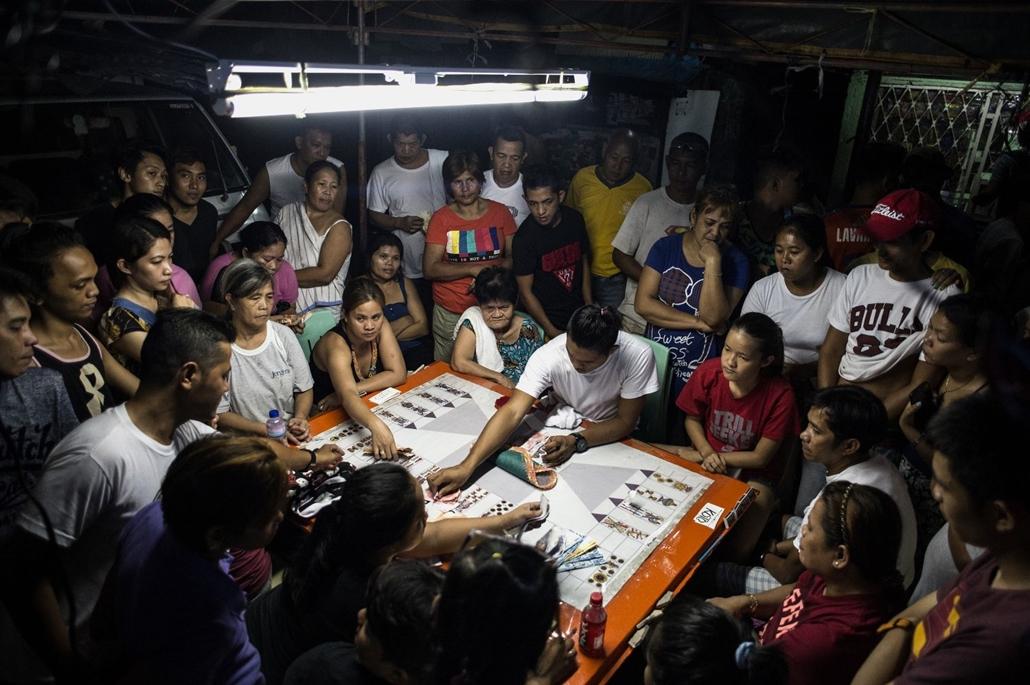 afp.16.10.29. Manila drogháború. Egy drogháborúban elhunyt rokonai kártyajáton játszanak, azt remélve, hogy így pénzt nyernek,melyből el tudják temetni az áldozatot.