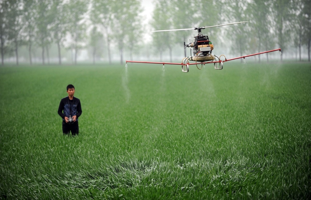 afp. hét képei - CHINA, Bozhou : This picture taken on April 15, 2014 shows a man controlling a drone to spray pesticides on a farm in Bozhou, central China's Anhui province. China's economy expanded 7.4 percent year-on-year in the first three months of t