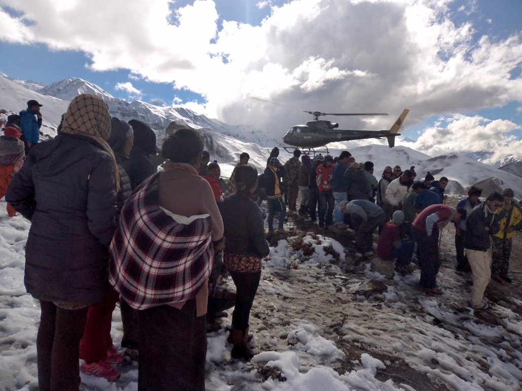 afp. hét képei - Manang, Nepál, 2014.10.15. In this handout photograph released by the Nepal Army on October 15, 2014, a Nepalese Army helicopter rescues survivors of a snow storm in Manang District, along the Annapurna Circuit Trek.  A snowstorm and aval