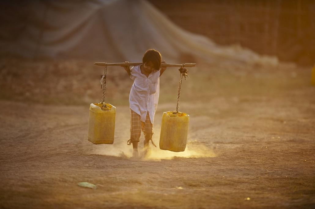 afp.14.03.11. - Yangon, Myanmar: vízhordó gyermek a helyi téglagyár mellett