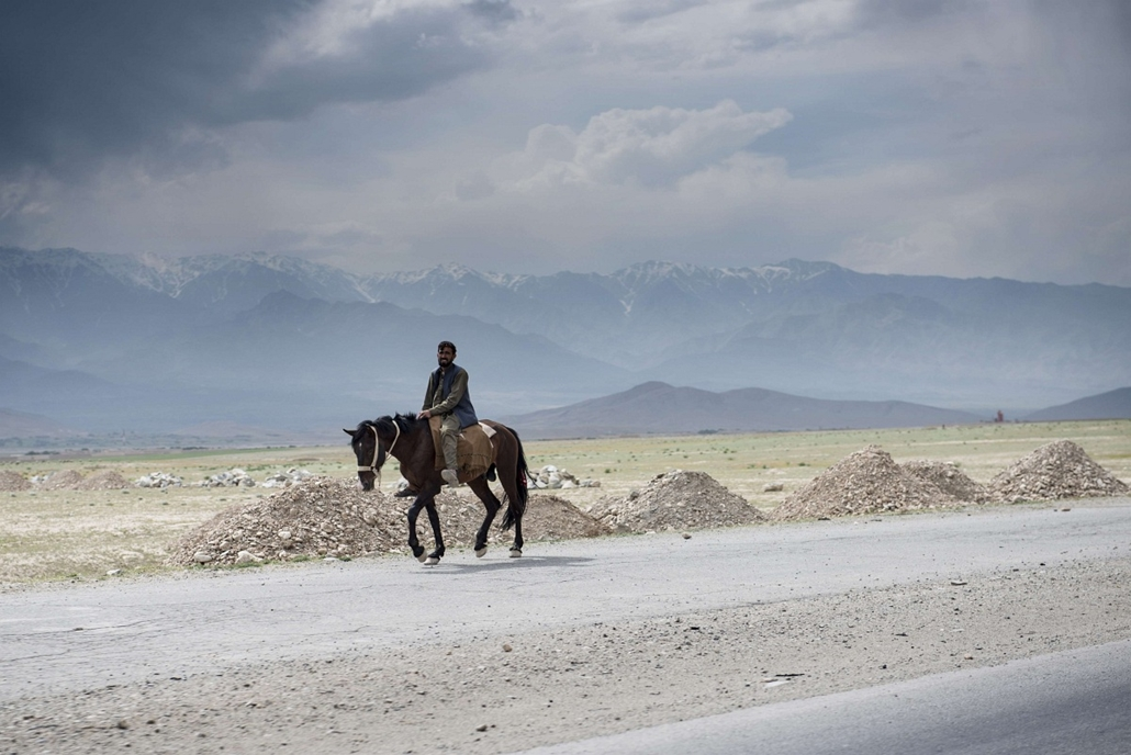 afp. nagyítás - hét képei - Parwan, Afganisztán, 2014.05.26. lovagló ember - A man rides a horse on the road to Bagram Airfield in Parwan on May 26, 2014. Afghanistan remains at war, with civilians among the hardest hit as the Taliban wage an increasingly