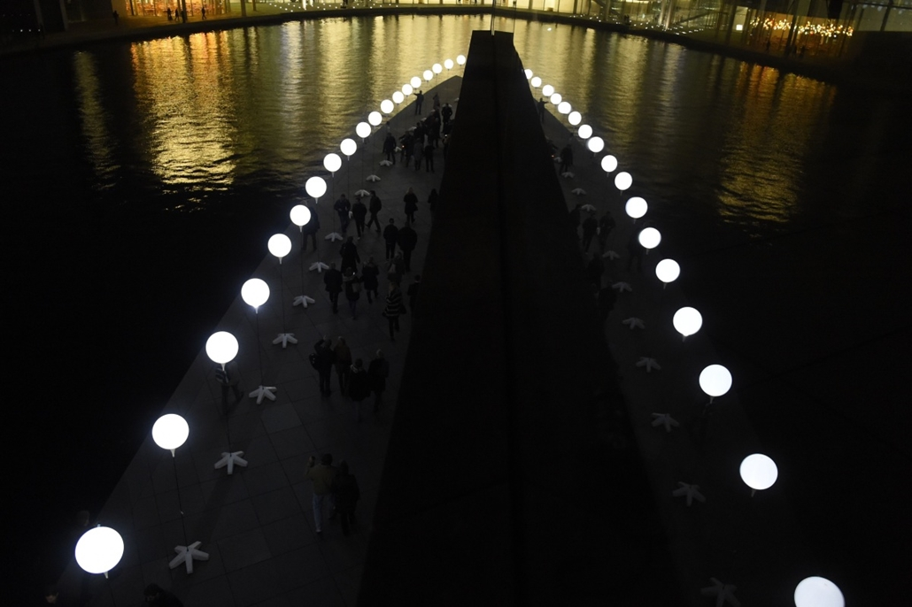 afp. Berlini fal leomlásA 25 éve 2014.11.09. The light installation Lichtgrenze (Light border) on the course of the former Berlin wall is reflected in a window near the Reichstag building on Spree River in Berlin on November 7, 2014. Germany kicked off ce