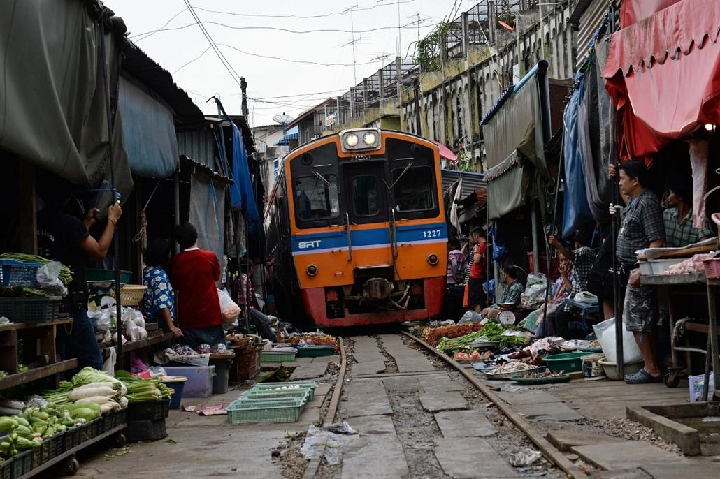 Maeklong, Thaiföld: vonat a helyi piacon. A ''Maeklong Railway Market'' különlegessége a rajta keresztülhaladó vasút, melyen ha szerelvény érkezik, az árusok egyszerűen csak behúzzák portékáikat, a vonat elhaladása után pedig visszapakolnak. - hét képei