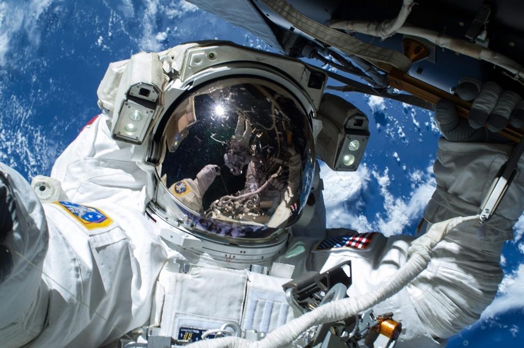 epa.15.02.25. - Világűr: Barry Wilmore űrhajós kábelt fektet a Föld körül keringő Nemzetközi Űrállomás külsején a munkához szükséges három tervezett űrséta első alkalmával - Terry Virts űrhajós tükröződik - 7képei