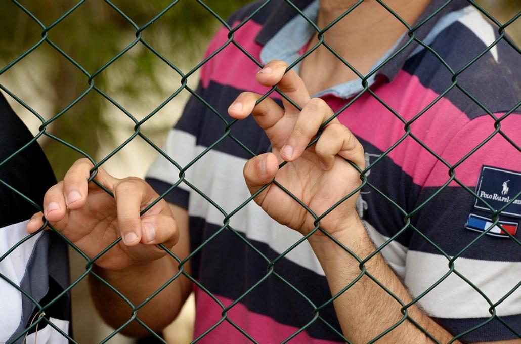 afp. hajóval érkező menekültek, migránsok, - Lampedusa, Olaszország, 2013.10.04. A migrant stands behind the fence at the Temporary Permanence Centre (CPT), a refugee camp in Lampedusa on October 4, 2013. Italy mourned today the 300 African asylum-seekers