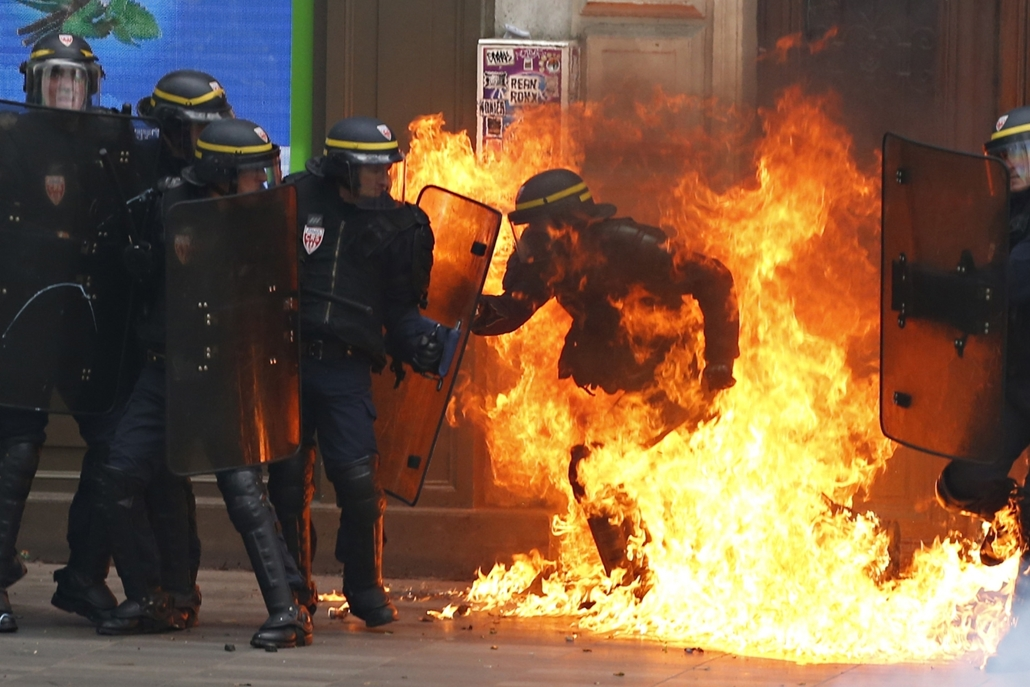 afp.16.09.15. - A French riot police officer is surrounded by flames, during a demonstration against the controversial labour reforms of the French government in Paris on September 15, 2016. Opponents of France's controversial labour reforms took to the s