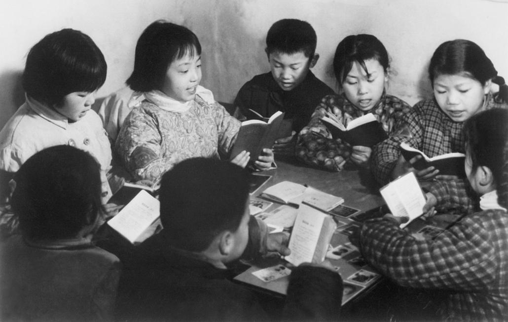 A tanulás útján: iskolás fiúk Mao Ce-tung kis piros könyvének tanulmányozása közben - könyv világnapja nagyítás