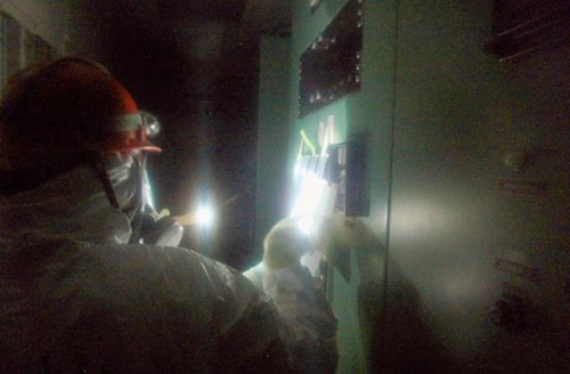 a Tokyo Electric Power Co. munkatársa egy mérőműszert néz a Fukusima-1 atomerőmű 1-es és 2-es reaktorblokkjának vezérlőtermében.