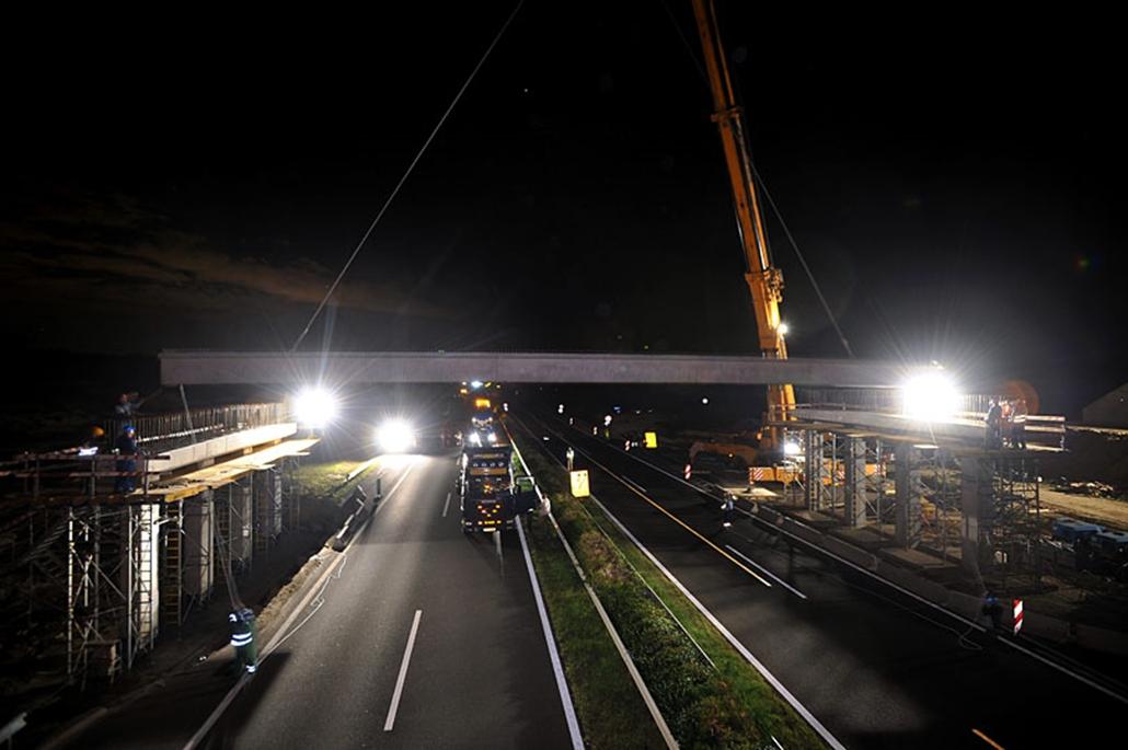 Egy daru a helyére emel egy betongerendát az M3-M31-es autópálya gödöllői csomópontjában épülő új, 83 méter hosszú híd munkálatainál. A felüljáró építéséhez 48 darab 28 méter hosszú, előre gyártott be