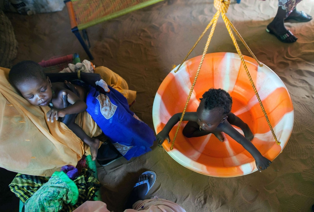 a hét képe nagyítás-fotógaléria kép - A handout picture released by the United Nations-African Union Mission in Darfur (UNAMID) shows a woman weighting a malnourished child at a clinic of the NGO Kuwait Patient Helping Fund in Abu Shouk camp for Internall