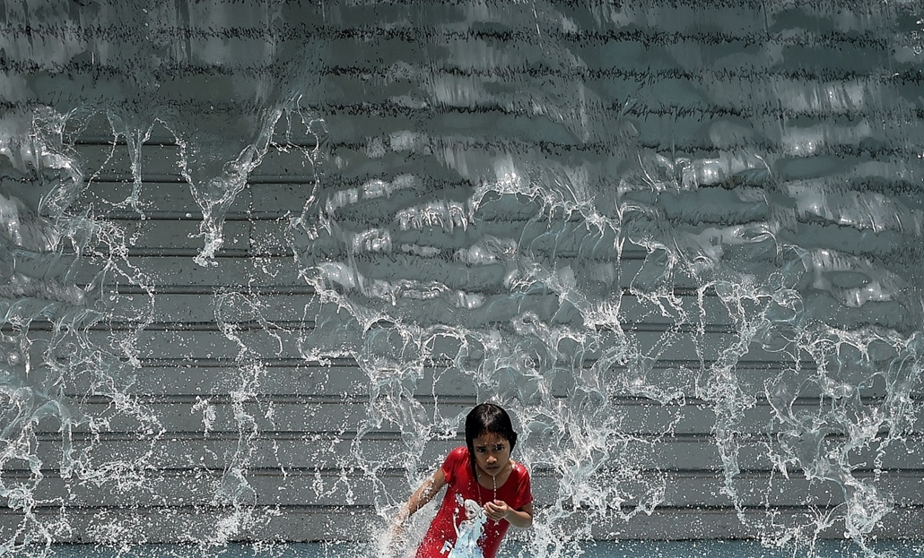 afp. hét képe - Kuala Lumpur, Malajzia 2015.03.18. kánikula, A young girl plays in an artificial waterfall on a hot day in Kuala Lumpur on March 18, 2015. Malaysia is currently experiencing a hot and dry weather spell.