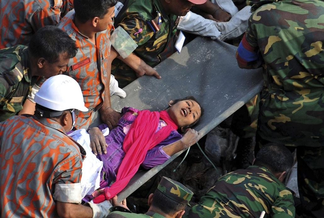 banglades, túlélő, összedőlt épület - Egy, az április 24-én összedőlt nyolcszintes ruhagyár romjai alól kiszabadított túlélőt visznek hordágyon a Dakkától 30 kilométerre fekvő Szavarban 2013. május 10-én.