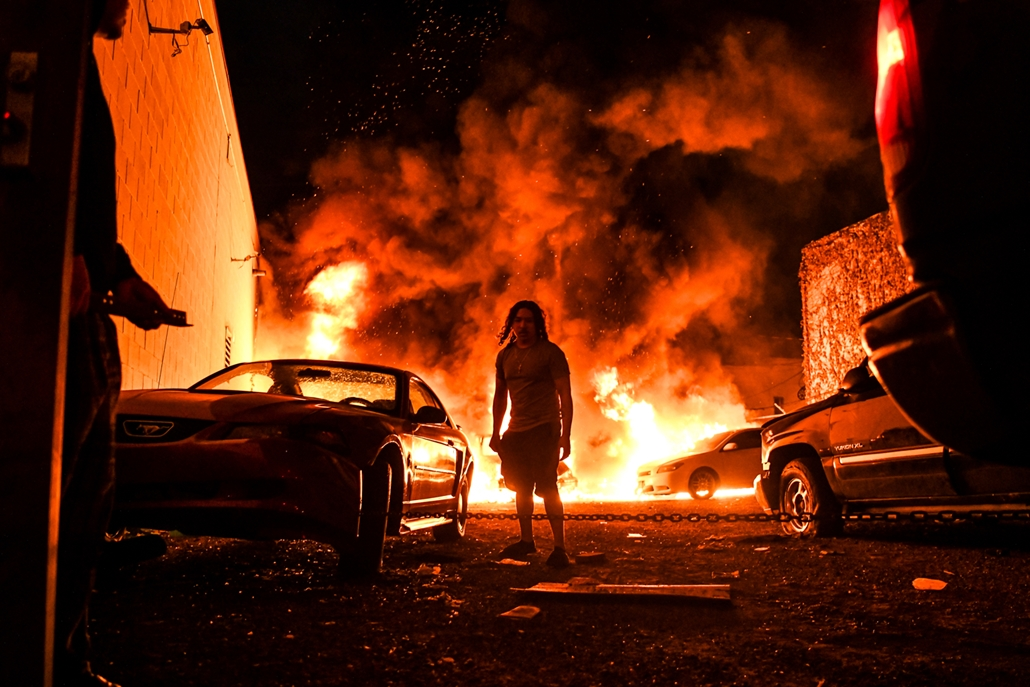 NAGYÍTÁS ÉV KÉPEI MÁJUS A man tries to toe away a car in a safe zone as the other car catches fire in a local parking garage on May 29, 2020 in Minneapolis, Minnesota, during a protest over the death of George Floyd, an unarmed black man, who died after a