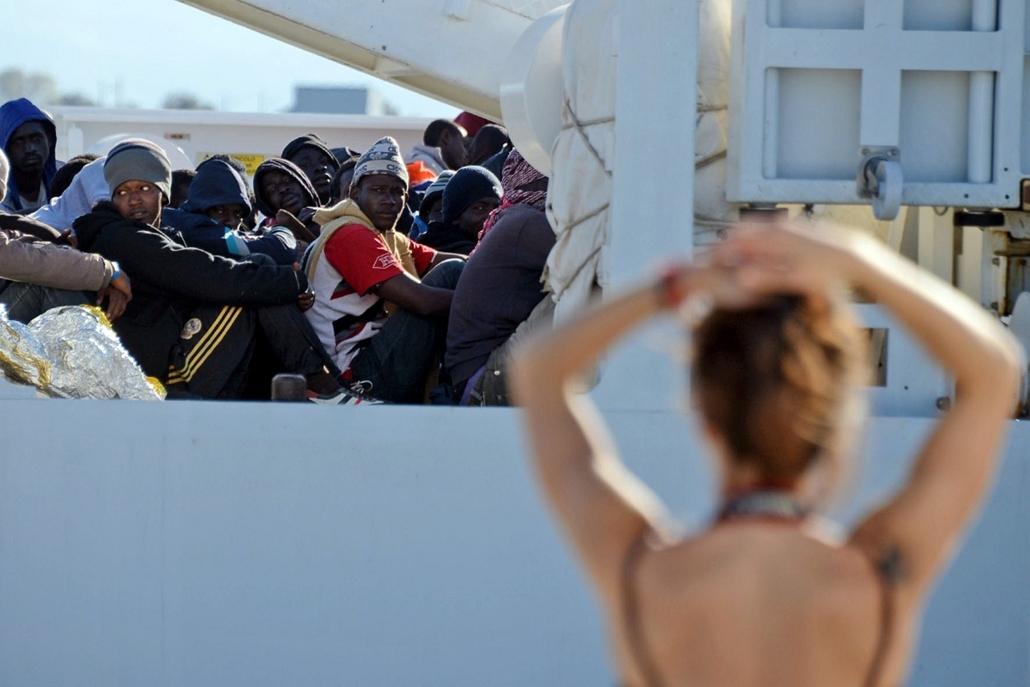 afp. hajóval érkező menekültek, migránsok, - 2015.04.16. Augusta, Olaszország, Shipwrecked migrants sit on the deck of a rescue vessel as they arrive in the Italian port of Augusta in Sicily on April 16, 2015.  As many as 41 migrants drowned after a small