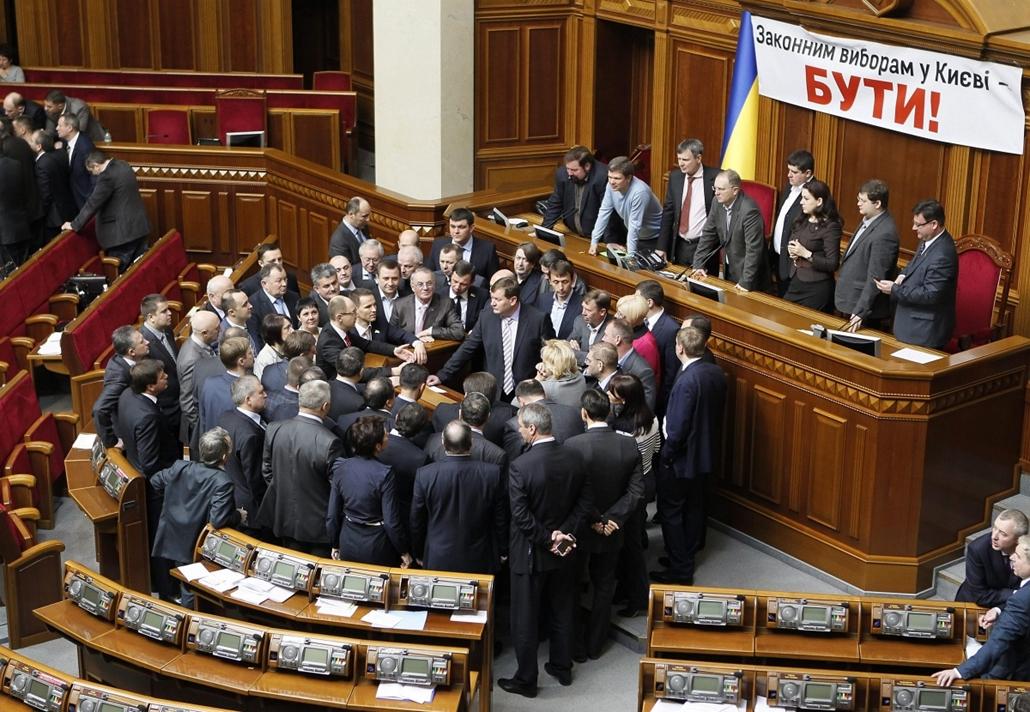Tüntetés az ukrán parlamentben Kijev, 2013. április 3. - Ellenzéki képviselők elállják az elnöki pulpitushoz vezető utat a kijevi parlament üléstermében 2013. április 3-án, miután a kormánypárt megakadályozta a kijevi polgármester-választás időpontjának k