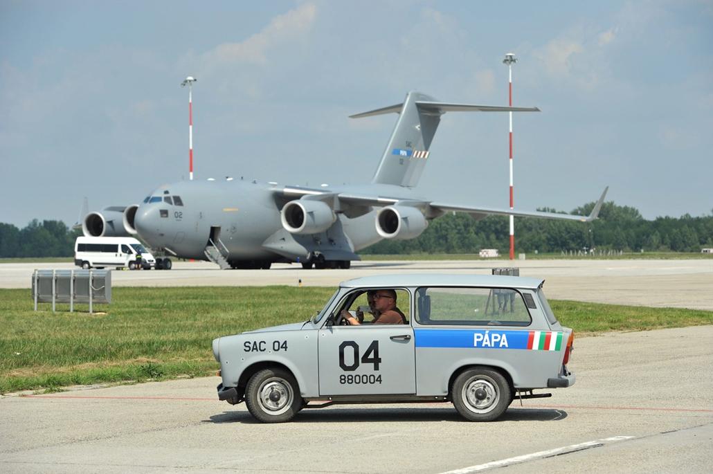 mti. Egy Boeing C-17-es teherszállító repülőgép és a kiszolgáló személyzet Trabantja  a pápai bázisrepülőtéren