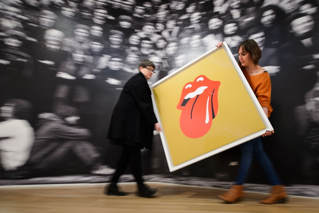 afp. hét képei - London, Egyesült Királyság, 2014.11.04. Rolling Stones, Gallery assistants pose for pictures with John Pasche's 1971 'Tongue and Lip Design' logo, commissioned by Mick Jagger, at a photocall for a retrospective of students' artwork, title