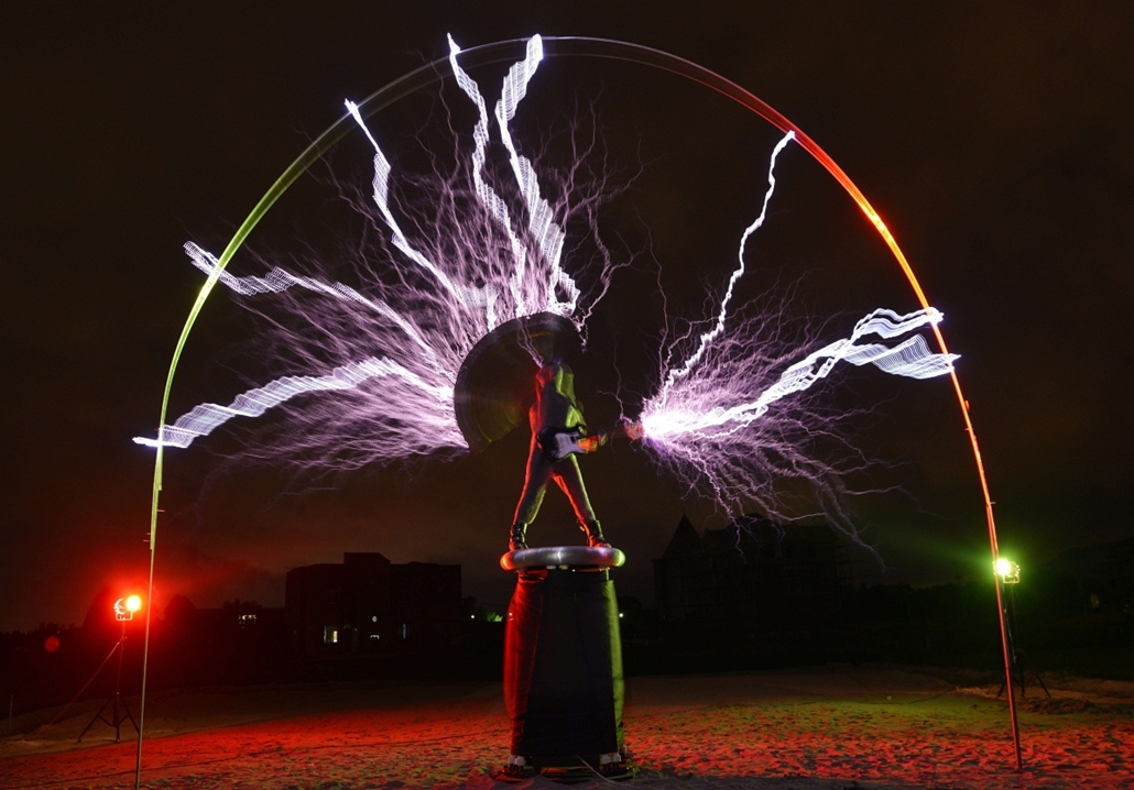 """Elektormos gitáros, The guitarist of the band """"Lightningfan"""" Wang Hongbin (C) creates lightning with a Tesla Coil in their village outside of Fuzhou in China's Fujian province on June 24, 2013. The Tesla Coil invented by Nikola Tesla in 1891 is a transfor"""
