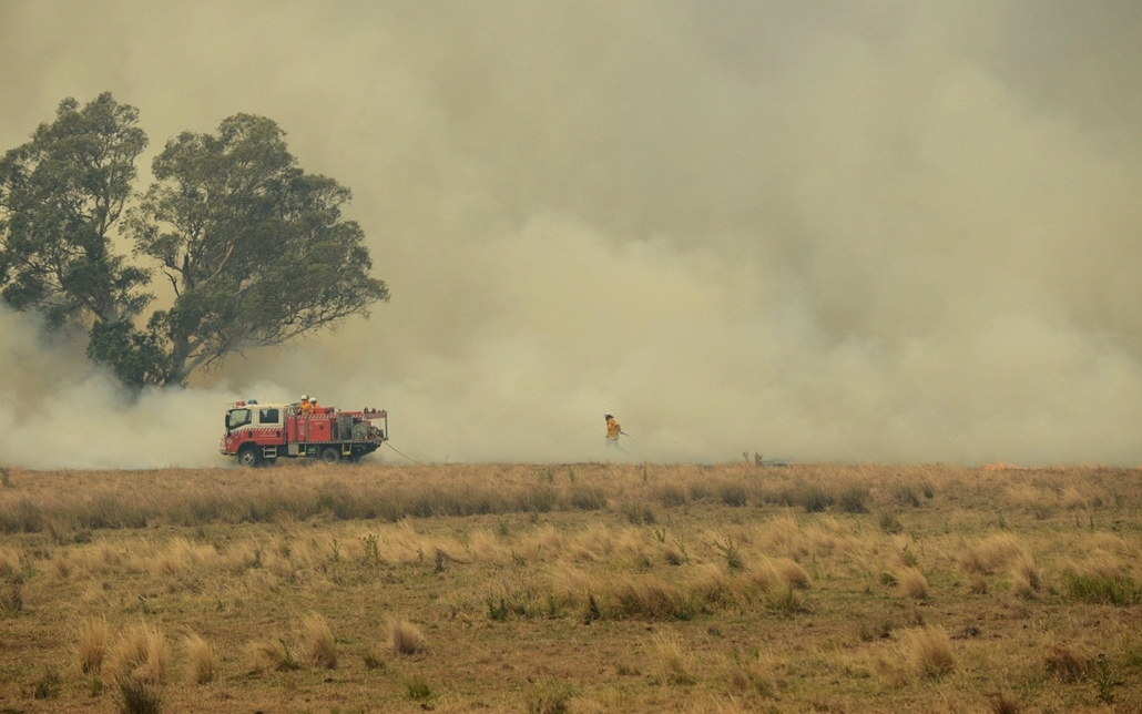 Bozóttűz Ausztráliában - Coonabarabran - Önkéntes tűzoltók próbálják megfékezni egy erdőtűz lángjait az Új-Dél-Wales szövetségi állambeli Coonabarabran közelében 2013. január 18-án. Ausztrália délkeleti országrészében bozóttüzek pusztítanak a rendkívüli h