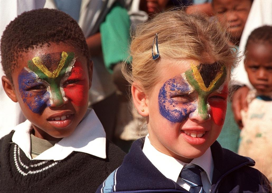 afp.97. - Két gyermek a dél-afrikai zászlót festette az arcára; a gyerekek Nelson Mandelát várják, aki felavat egy új iskolát Fokvárosban. - Apartheid nagyítás