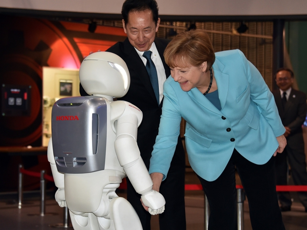 afp. Tokió, Japán, Angela Merkel robottal találkozik, 2015.03.09. German Chancellor Angela Merkel (R) shakes hands with Japanese auto giant Honda Motor's humanoid robot Asimo (L) as museum head and former astronaut Mamoru Mori (C) looks on at the National