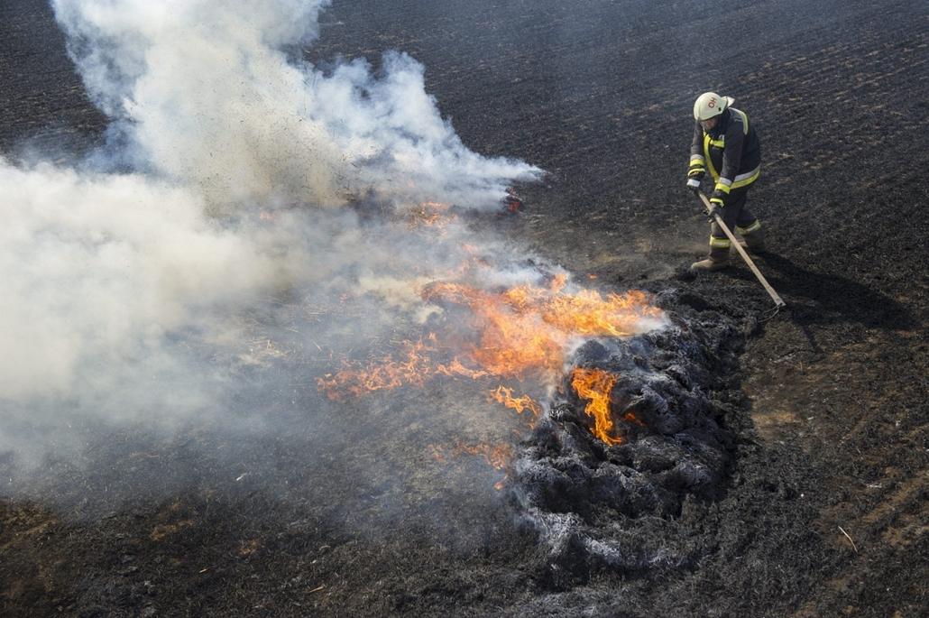 mti. a hét képei 0616-0621 - 2014.06.19. Orosháza, 2014. június 19. Tűzoltó dolgoznik az égő szalmabálák és a tarló oltásán Orosháza határában 2014. június 19-én. 200 bála kapott lángra a 10 hektáros területen.