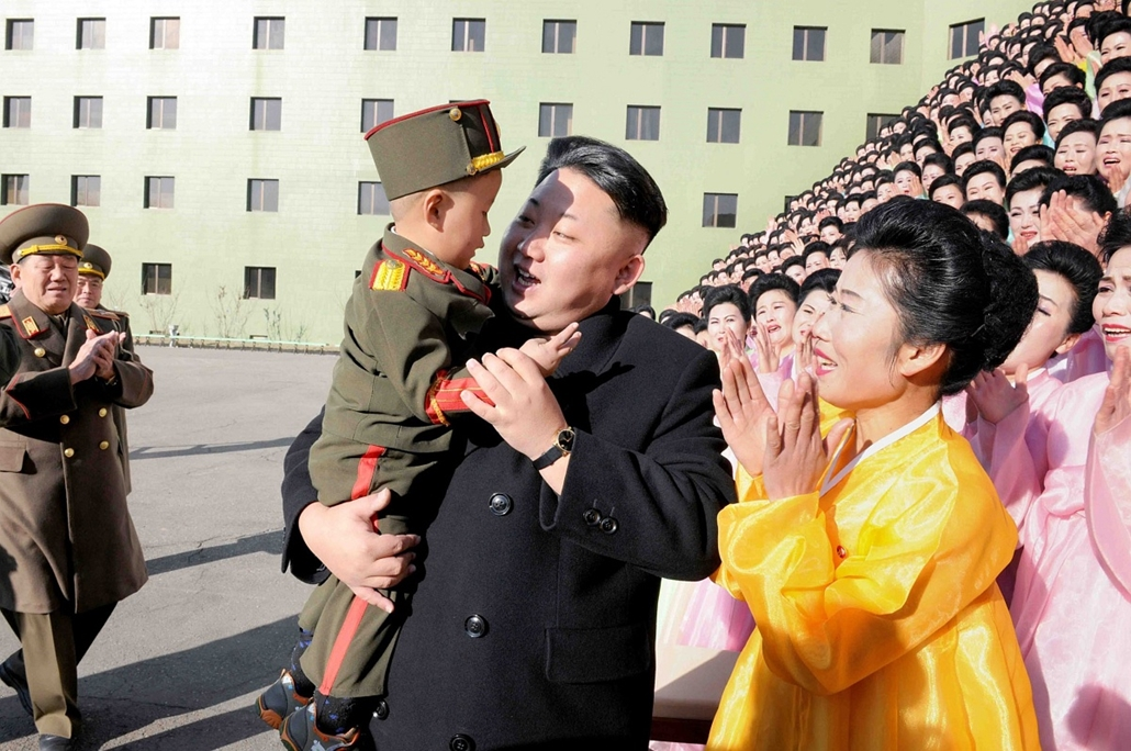 afp. hét képei - 2014.12.09. Kim Dzsong Un, This undated picture released from North Korea's official Korean Central News Agency (KCNA) on December 9, 2014 shows North Korean leader Kim Jong-Un (C) holding up a boy as he joins a photo session with the par
